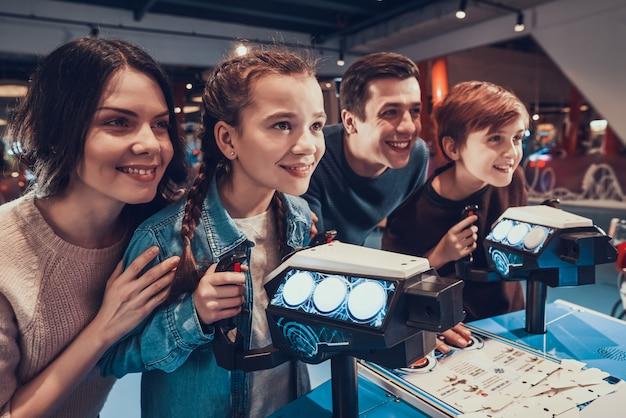 Filho e filha estão pilotando naves espaciais jogando no arcade.