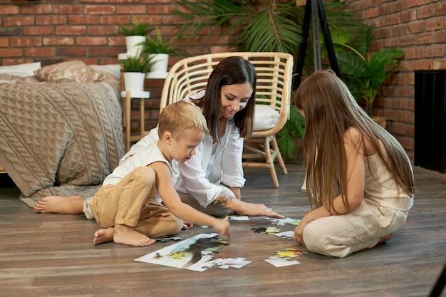 Filho e filha mãe montaram o quebra-cabeça no chão. entretenimento familiar. mulher, menina e menino brincando juntos
