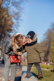 Filho e mãe brincando juntos no parque. dia das mães.