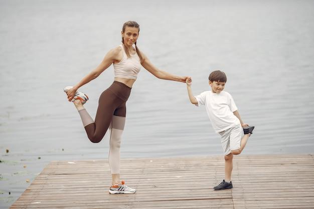 Filho e mãe estão fazendo exercícios no parque de verão. família perto da água.