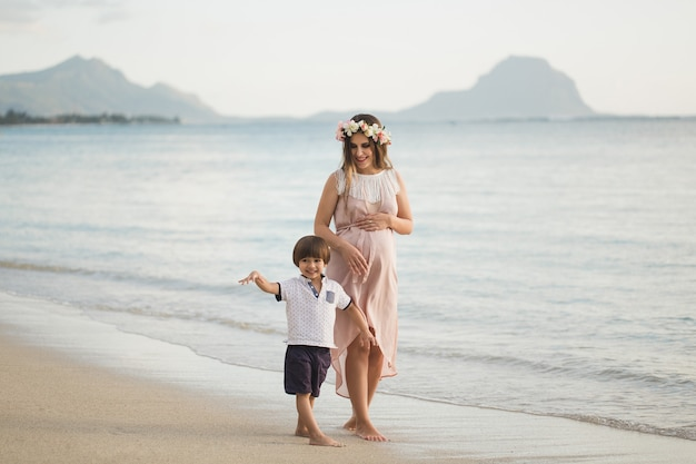 Filho e mãe grávida na praia.
