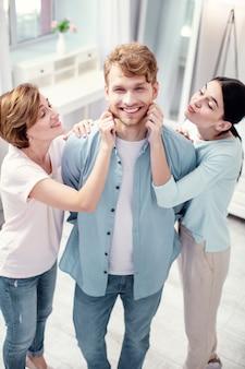 Filho e marido. jovem alegre sorrindo enquanto aprecia estar no centro das atenções
