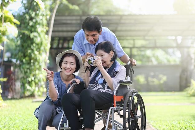 Filho e nora cuidando de mãe idosa no quintal