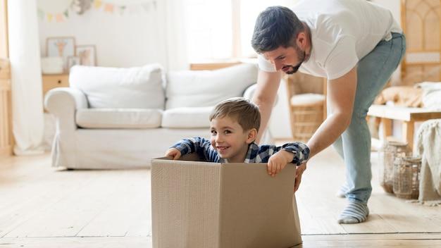 Filho e pai brincando com uma caixa