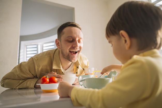 Filho e pai comendo na cozinha