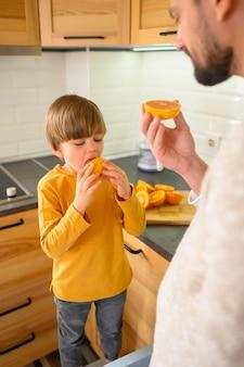 Filho e pai comendo uma laranja