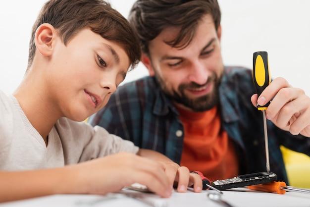 Filho e pai consertando um telefone