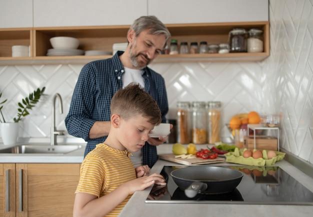 Filho e pai cozinhando tiro médio