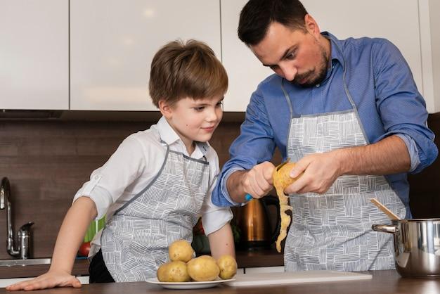 Filho e pai de ângulo baixo, limpeza de batatas