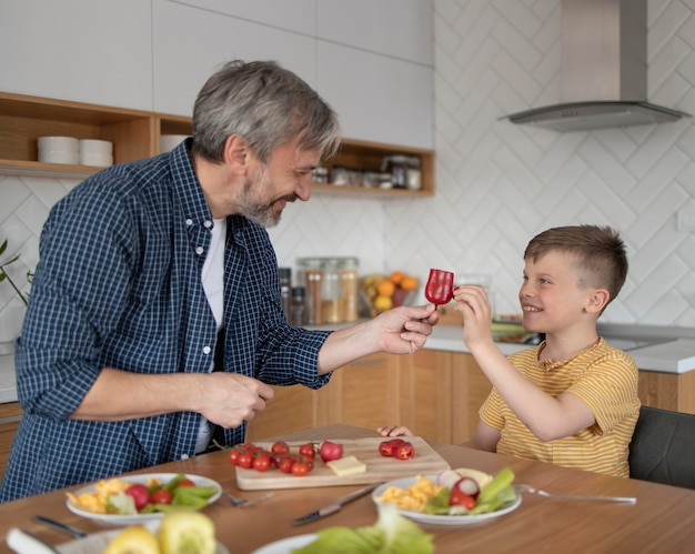 Filho e pai de dose média com vegetais