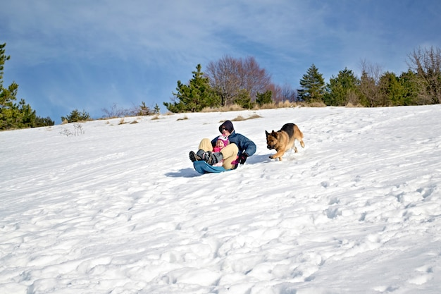 Filho e pai em trenó nas montanhas no inverno