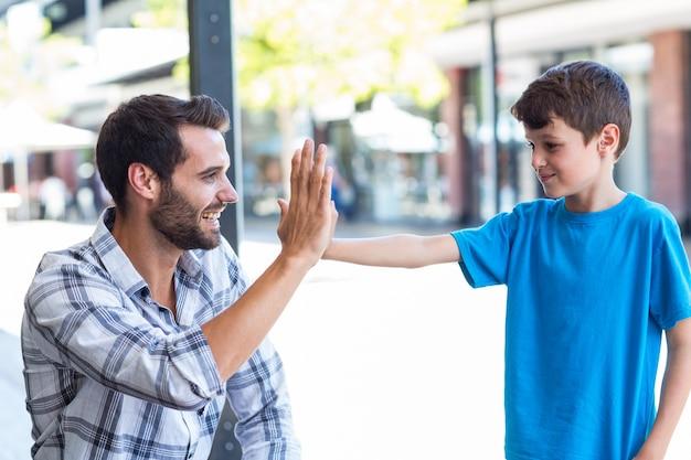 Filho e pai fazendo alta cinco