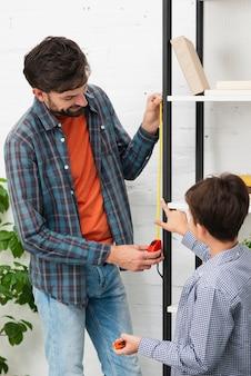 Filho e pai medindo um auto