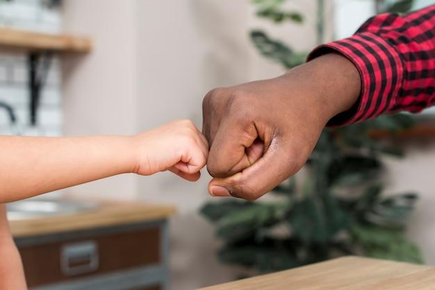 Filho e pai negro batendo os punhos