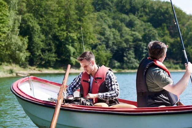 Filho e pai no barco fazem os preparativos para os peixes