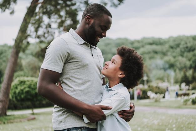 Filho e pai, olhando e abraçando uns aos outros.