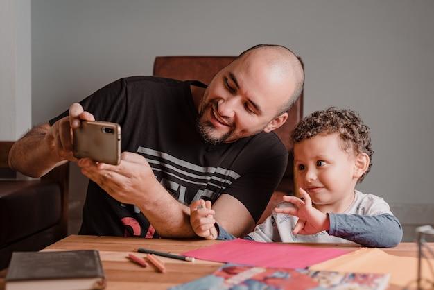 Filho e pai olhando para o celular enquanto fazem a lição de casa