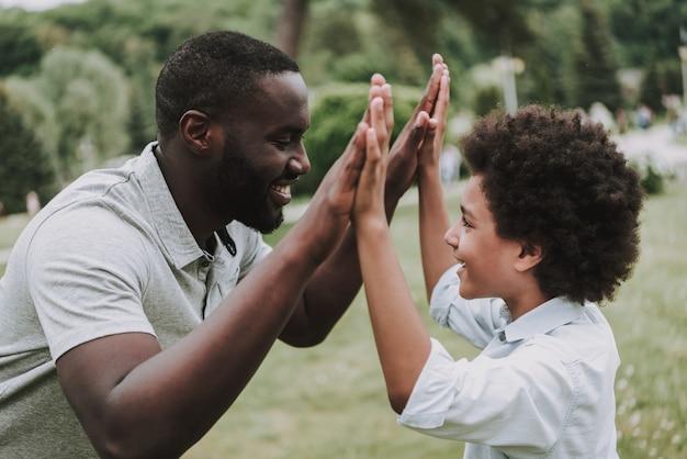 Filho e pai olhando uns aos outros e dar cinco