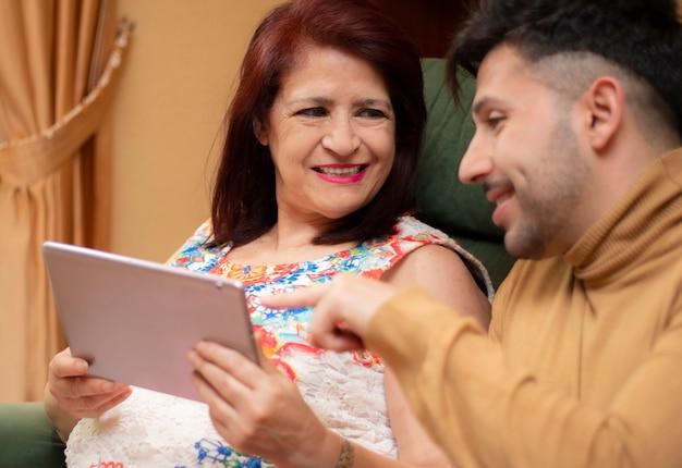 Filho, ensinando sua mãe a usar o tablet. idosos usando tecnologia