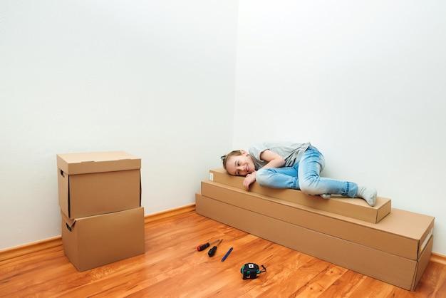 Filho feliz deitado em uma grande caixa de papelão