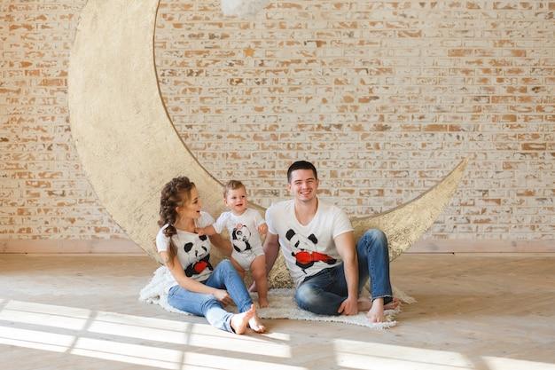 Filho feliz do pai, da mãe e da criança da família perto de uma parede de tijolo vazia na sala.