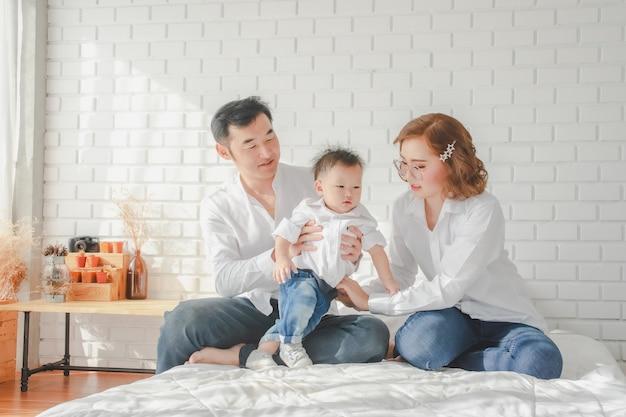 Filho japonês asiático da mãe do pai da família que veste a criança levando da camisa branca no quarto na sala branca.