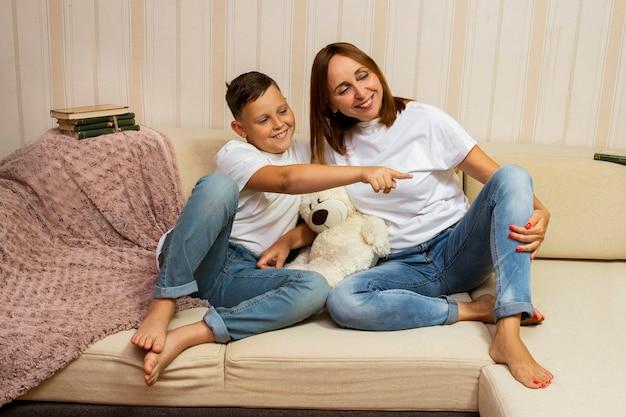 Filho mostrando algo para sua mãe no lado direito. eles passam seu tempo livre juntos. mãe e filho felizes e se amam.