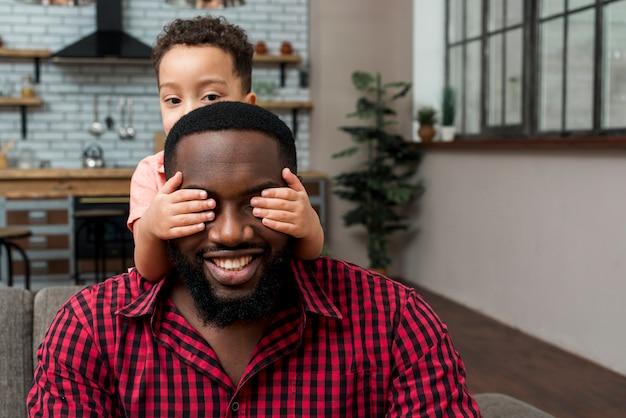 Filho negro, cobrindo os olhos do pai