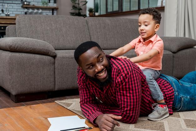 Filho negro e pai se divertindo no chão