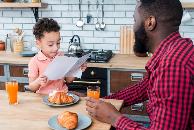 Filho negro, lendo o cartão enquanto tomando café da manhã com o pai