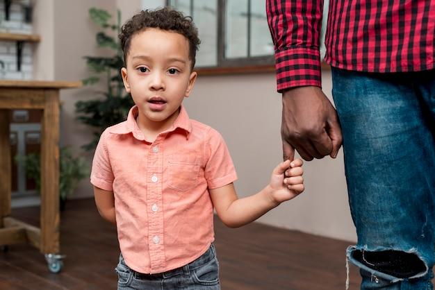 Filho negro segurando a mão de pais