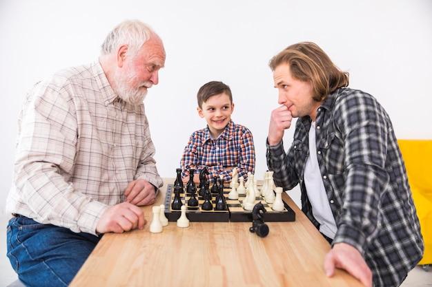Filho, olhando o pai e o avô jogando xadrez
