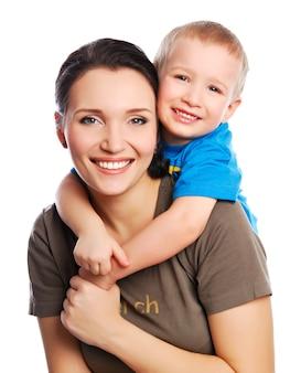 Filho pequeno abraçando sua linda jovem mãe