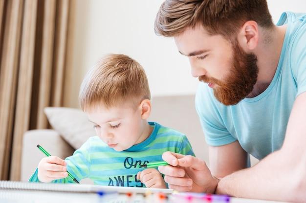 Filho pequeno e pai desenhando com marcadores juntos em casa