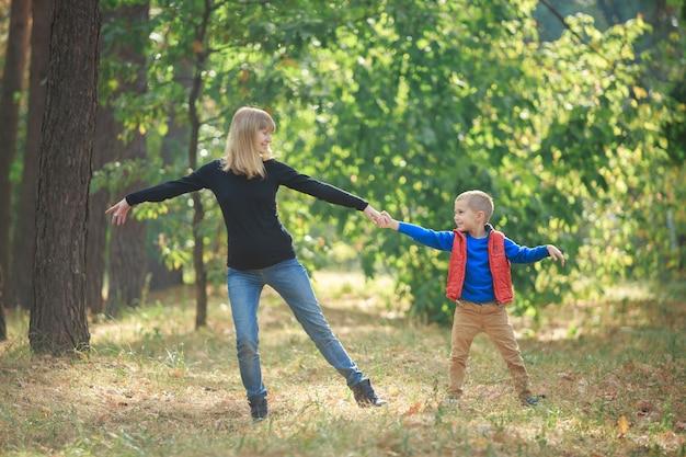Filho pequeno e sua mãe grávida brincando na natureza. menino e mulher grávida sorridente caminhando ao ar livre no parque verde. jovem família feliz esperando bebê. mulher grávida, aproveitando o tempo com seu filho