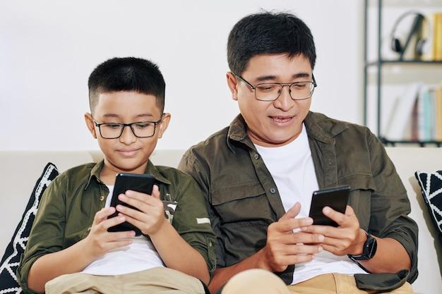 Filho pré-adolescente e seu pai maduro sentados no sofá e em casa jogando em smartphones