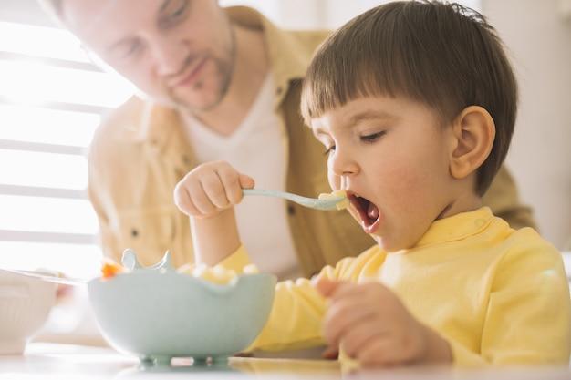 Filho pronto para dar uma grande mordida em sua comida