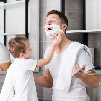 Filho raspando as bochechas e o queixo do pai no banheiro