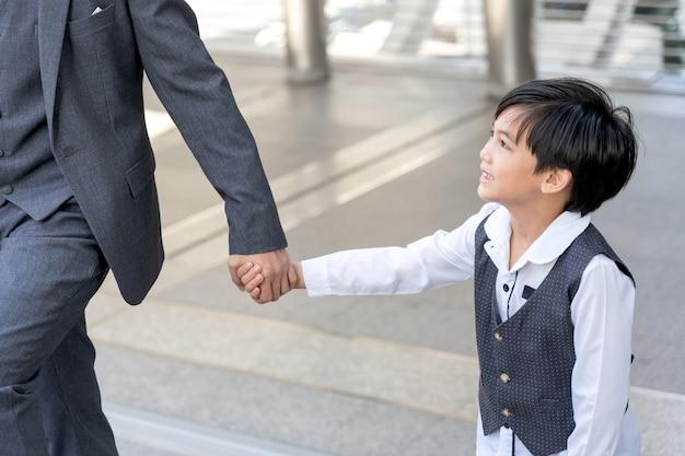 Filho segurando a mão do pai em distrito comercial urbano