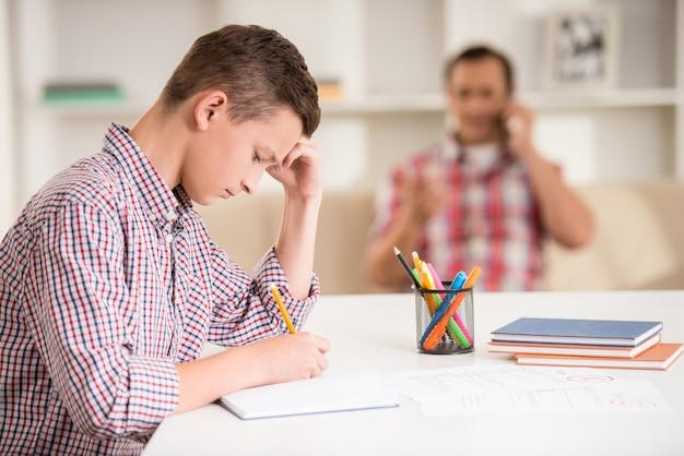 Filho sentado na mesa enquanto seu pai falando no telefone.