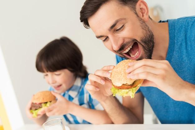 Filho sorridente e pai almoçam na cozinha.