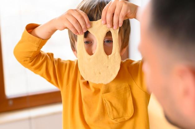 Filho, vestindo uma máscara de massa engraçada