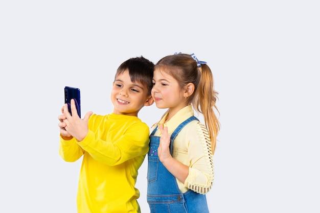Filhos bonitos com smartphone falam sobre comunicação por vídeo em fundo branco. a garota acena com a mão em saudação.