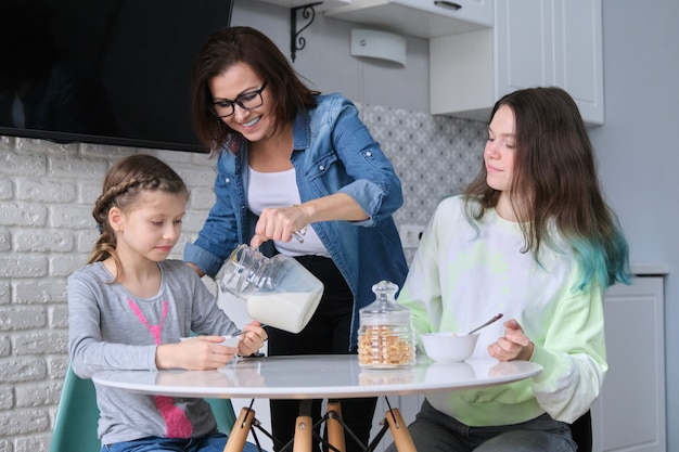 Filhos com a mãe comendo em casa na cozinha, duas meninas sentadas à mesa com pratos de flocos de milho e leite
