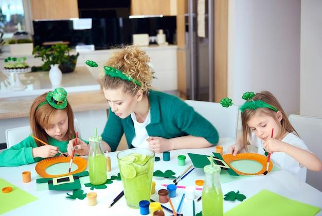 Filhos com a mãe fazendo decorações