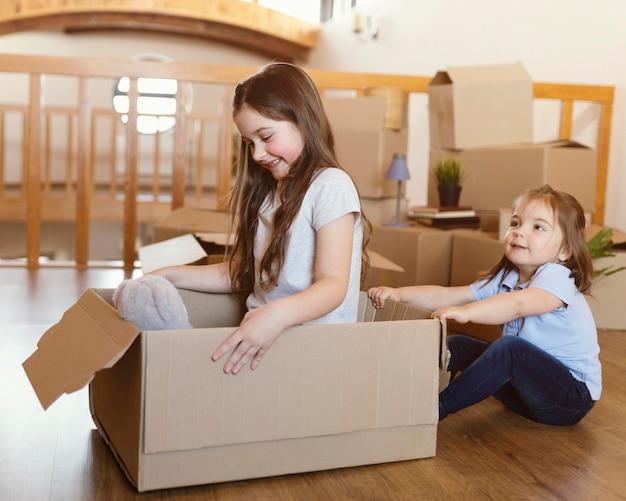 Filhos completos brincando com a caixa