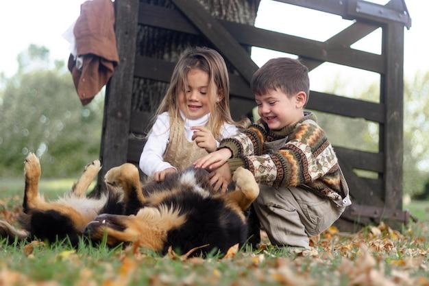 Filhos completos brincando com um cachorro