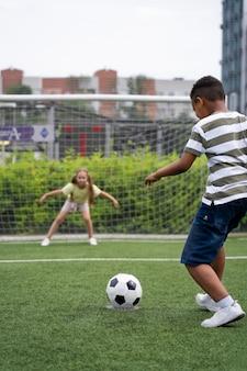 Filhos completos jogando futebol no campo
