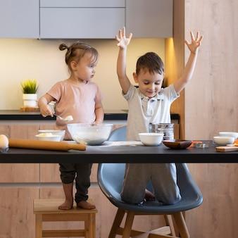 Filhos completos se divertindo na cozinha