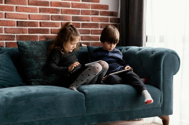 Filhos completos segurando dispositivos